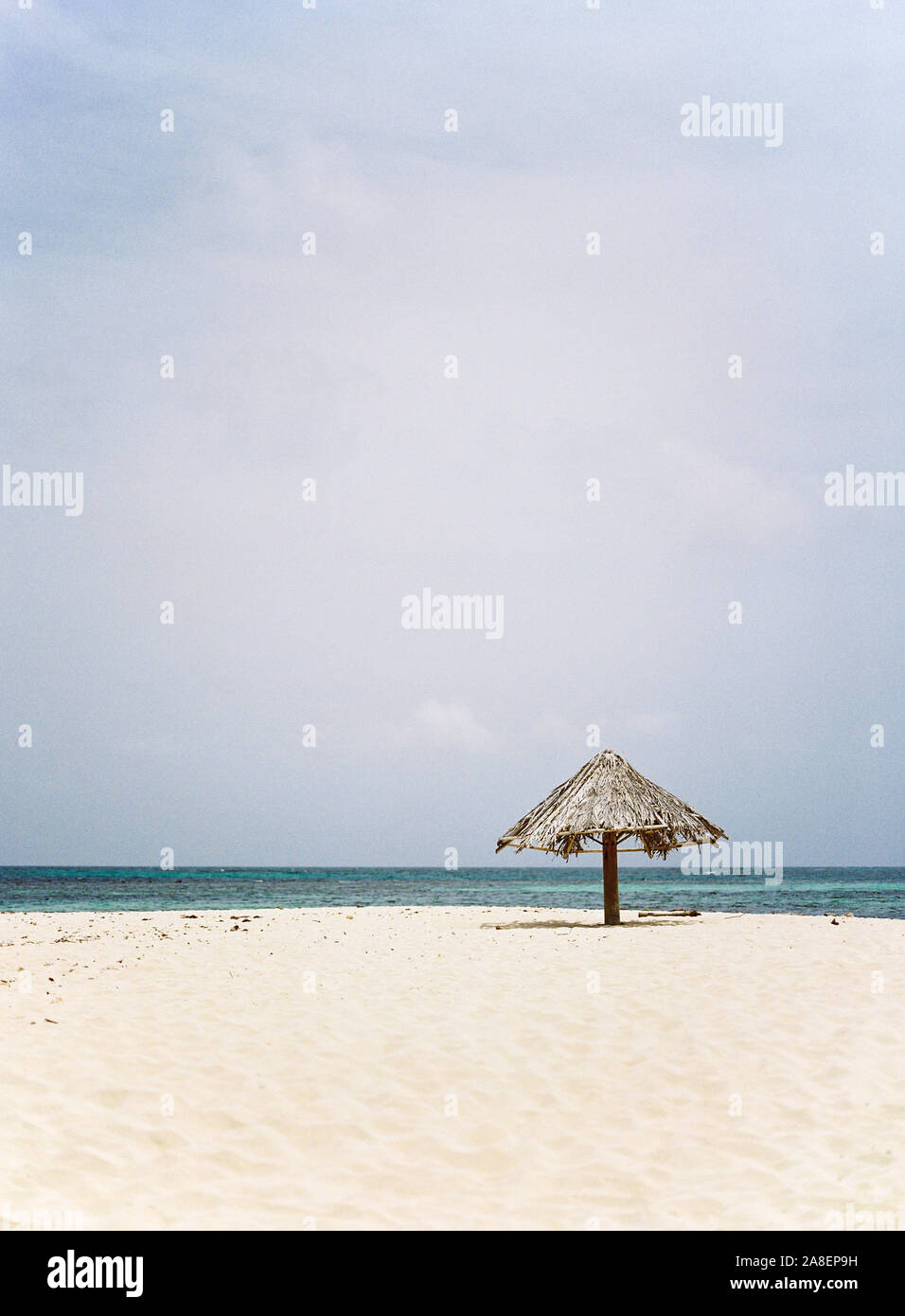 A palm frond umbrella resting on the isolated island beach of Mopion in St. Vincent and the Grenadines. Stock Photo