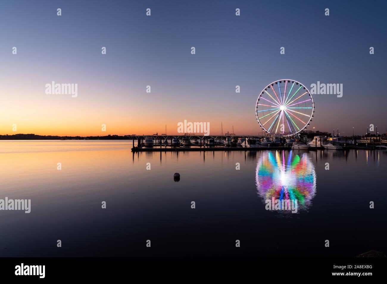 Illuminated ferris wheel at National Harbor near the nation capital of Washington DC at sunset Stock Photo