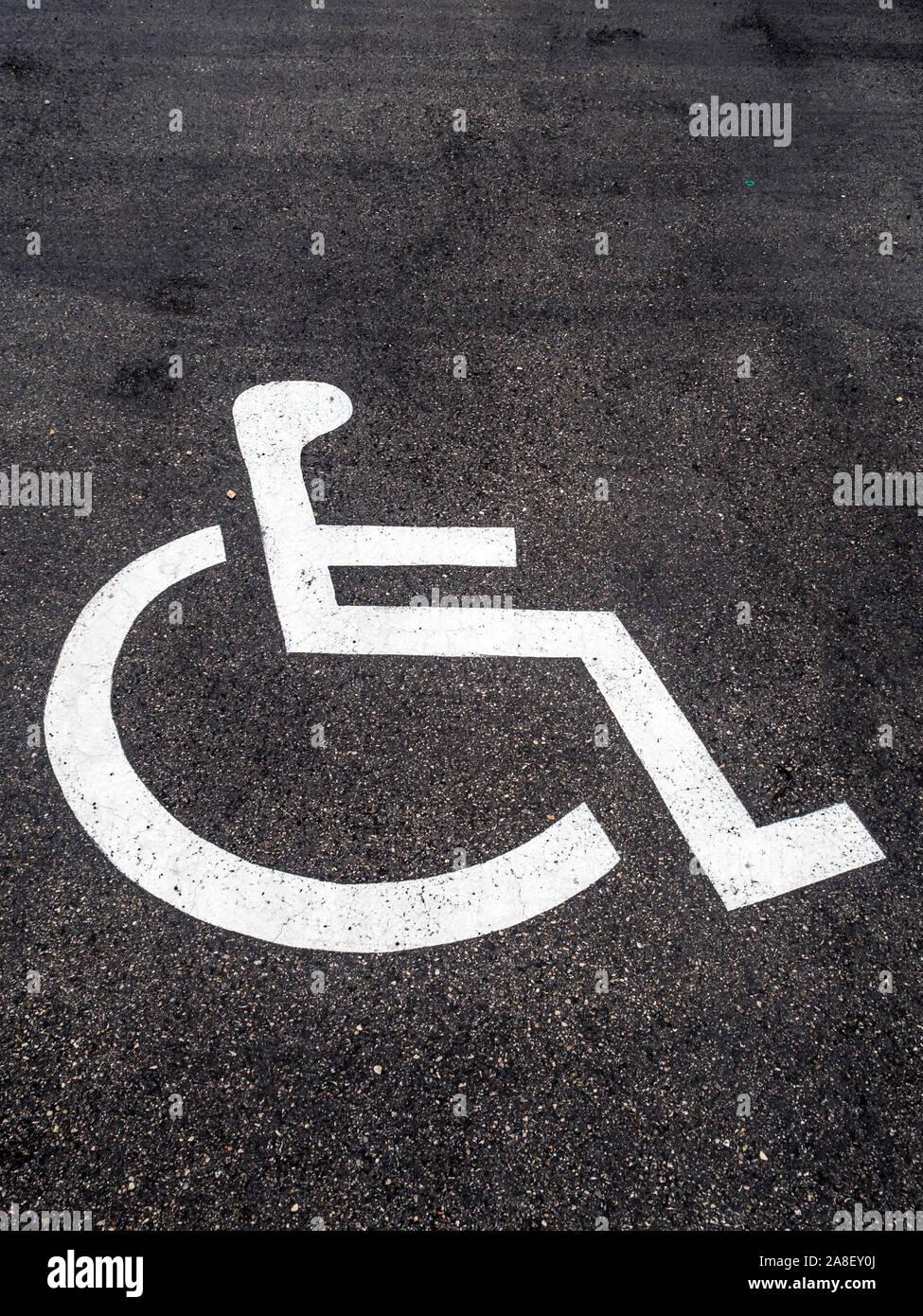 Ein Rollstuhl ist auf einem Parkplatz für Behinderte angebracht. Stock Photo
