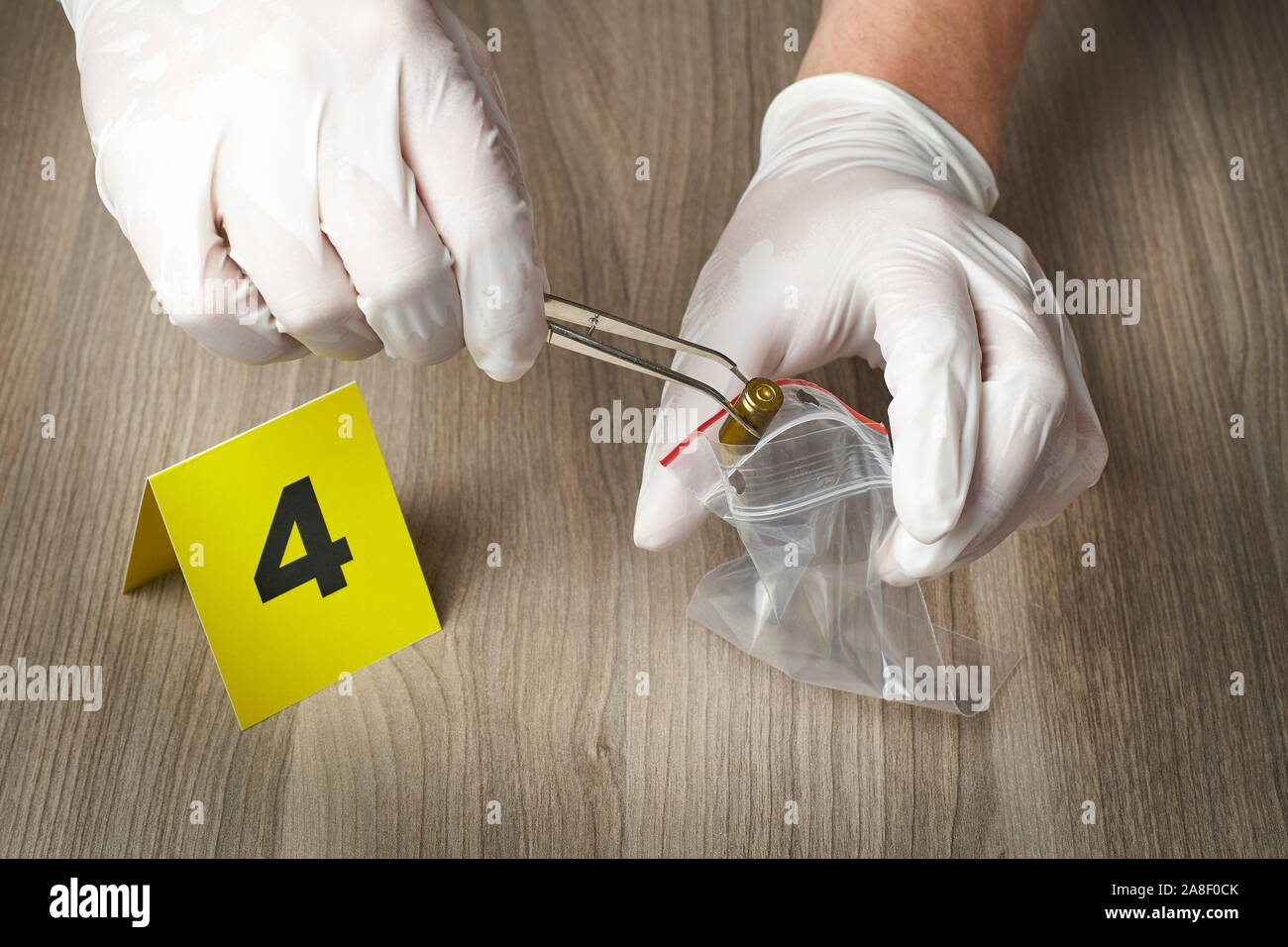 Crime Scene Investigation Forensic Officer Collecting A Bullet Casing As A Piece Of Evidence Stock Photo Alamy