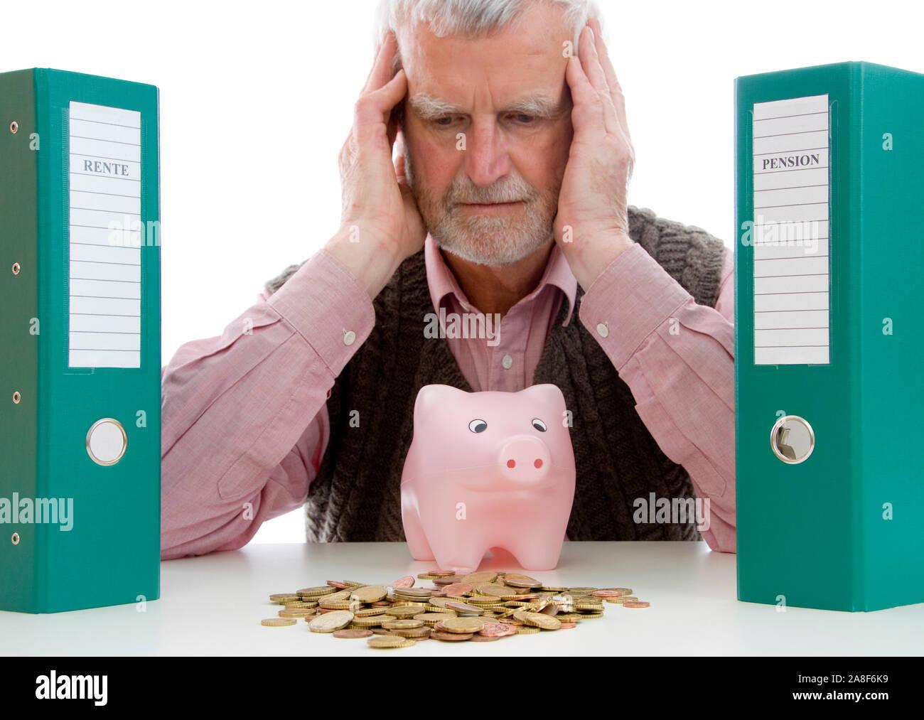 Rentner mit Geldsorgen, sitzt vor Sparschwein und verzweifelt, MR: Yes Stock Photo