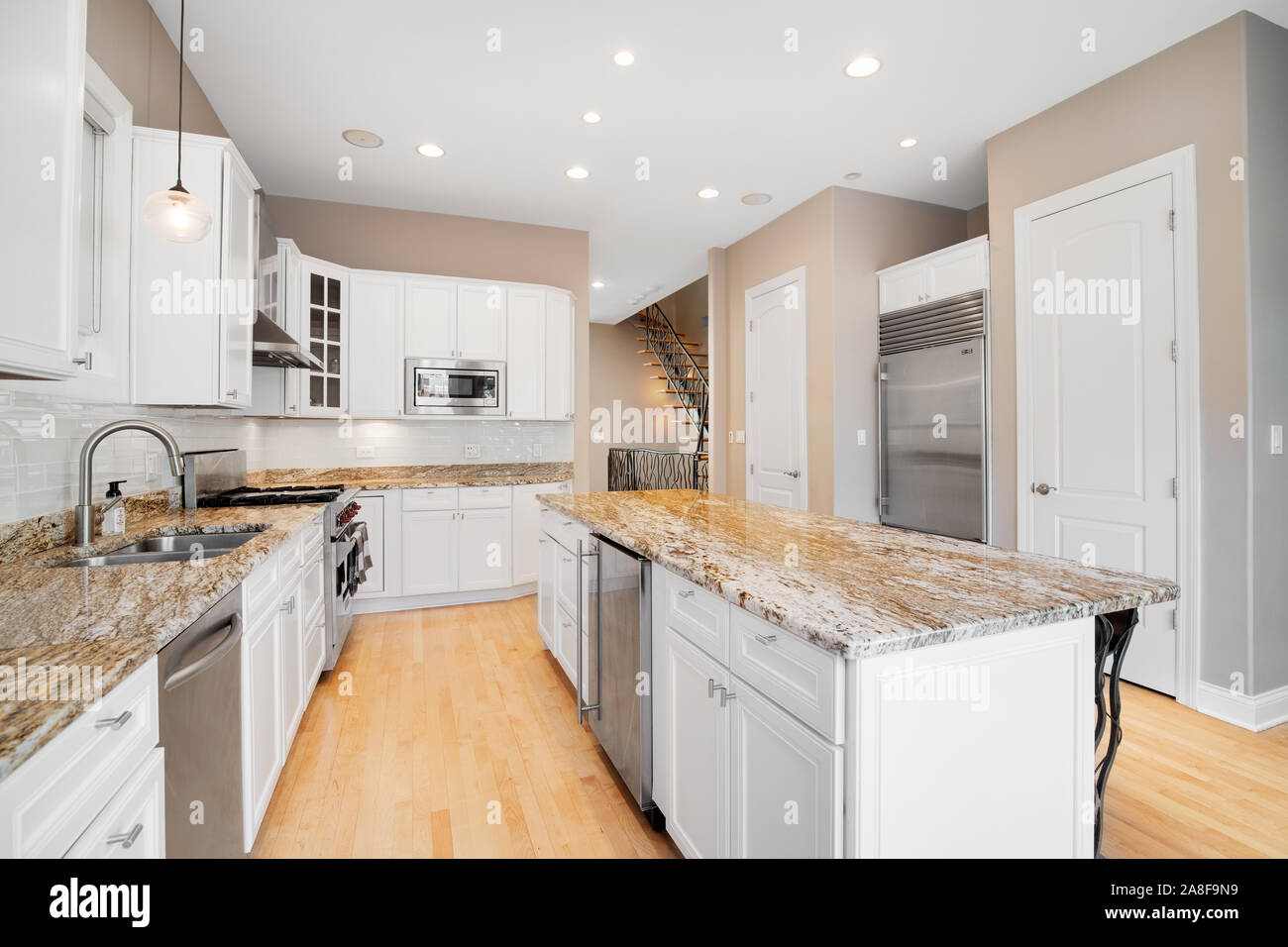A large white kitchen in a luxurious home with wood floors ...
