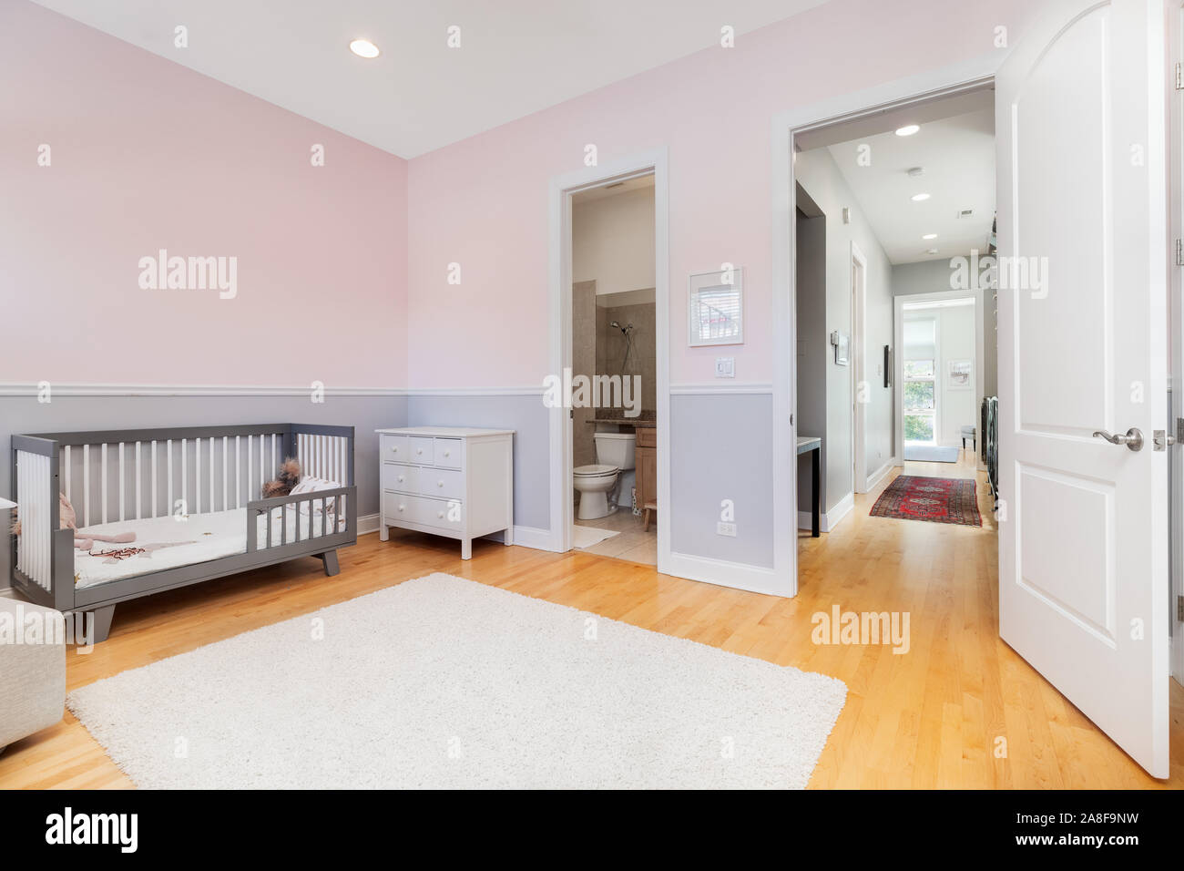 A Children S Bedroom With White And Purple Walls Looking Down The Hallway A Crib Sits Up Against The Wall And A Rug Over The Light Hardwood Floors Stock Photo Alamy