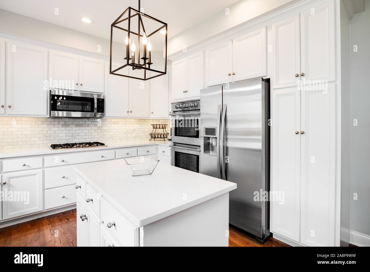 A Bright Kitchen With White Cabinets White Granite Counter Tops Stainless Steel Appliances And Light Fixture Hanging Over The Island Stock Photo Alamy,Small Town Definition