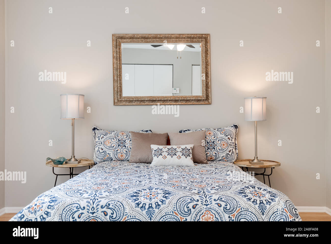 A Bed Centered In The Master Bedroom Of A Residence With Two Lamps On The Nightstand And A Mirror Hangs Above The Bed Stock Photo Alamy