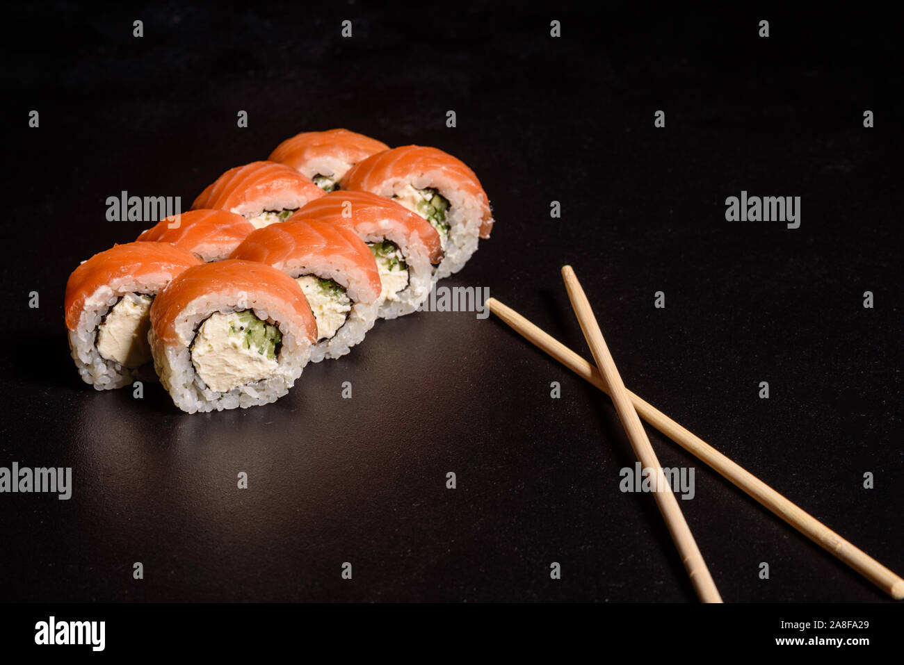 Various kinds of sushi served on a dark background. Roll with salmon, avocado, cucumber. Sushi menu. Japanese food. Stock Photo