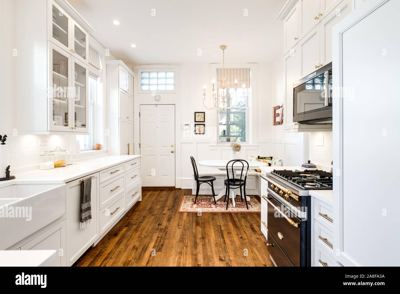 A white kitchen with a small dining room area in the corner and