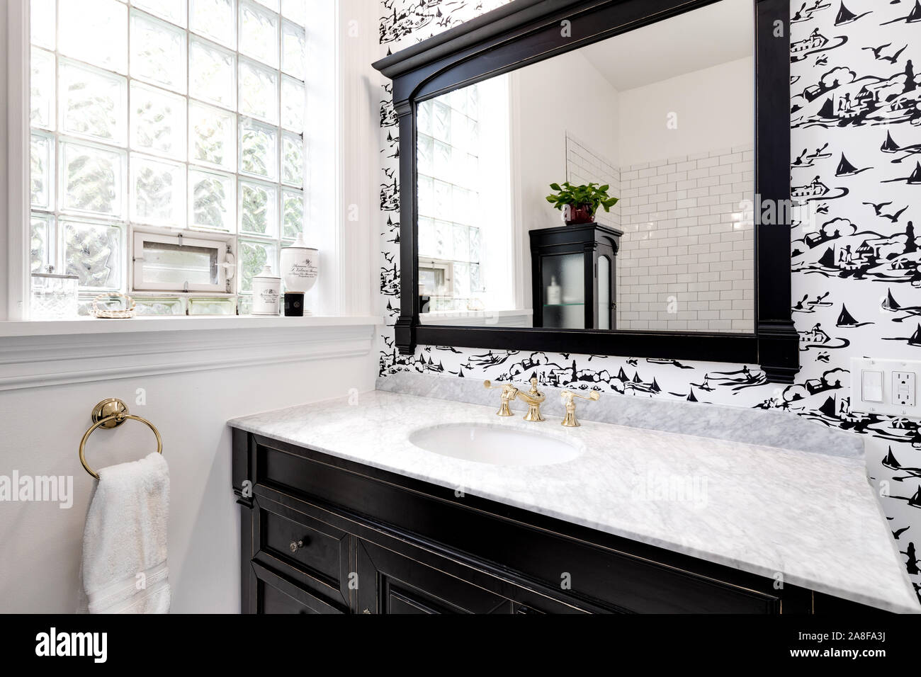 A Luxurious Bathroom In A Downtown Chicago Condo With Granite And Gold Hardware Dark Wood Vanity And An Accent Wall With Black And White Wallpaper Stock Photo Alamy