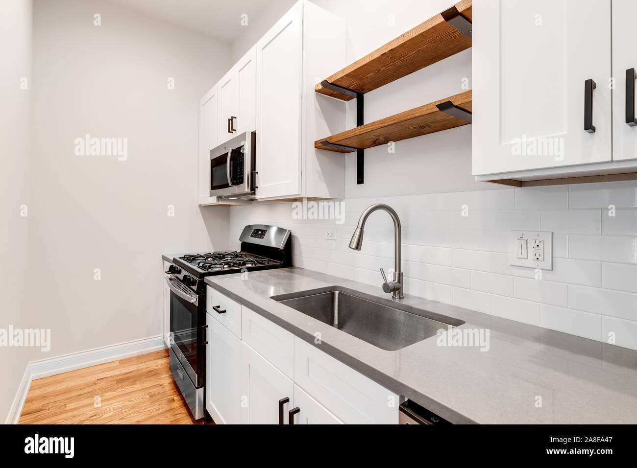 A small kitchen in a Chicago condo with white cabinets and GE ...
