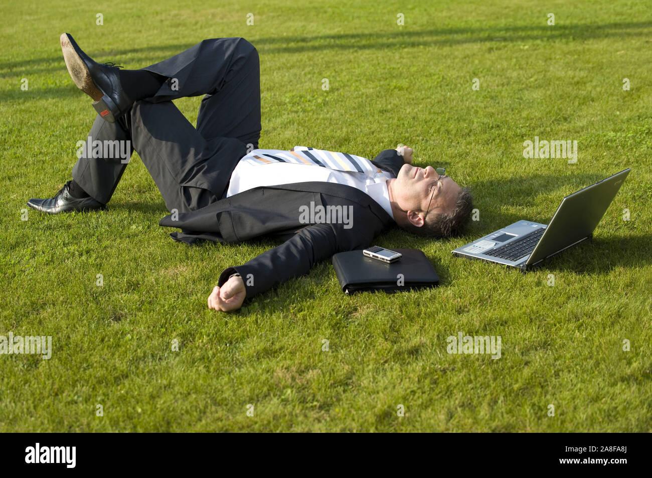 Geschäftsmann sitzt auf einer Wiese, schläft, ruht, Pause, Mittagspause, Burn Out, Laptop, Computer, MR:Yes Stock Photo