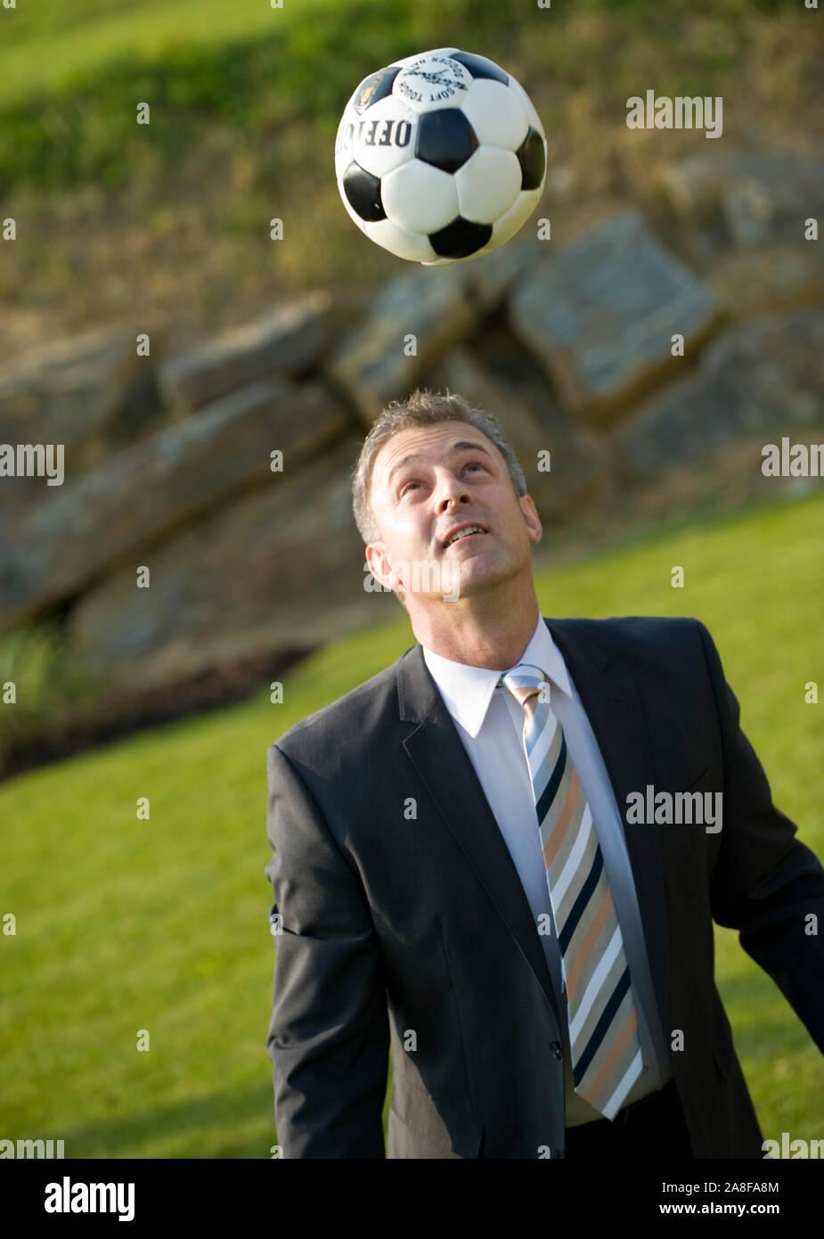 Gecshäftsmann spielt Fussball, Pause, Mittagspause,  MR:Yes Stock Photo