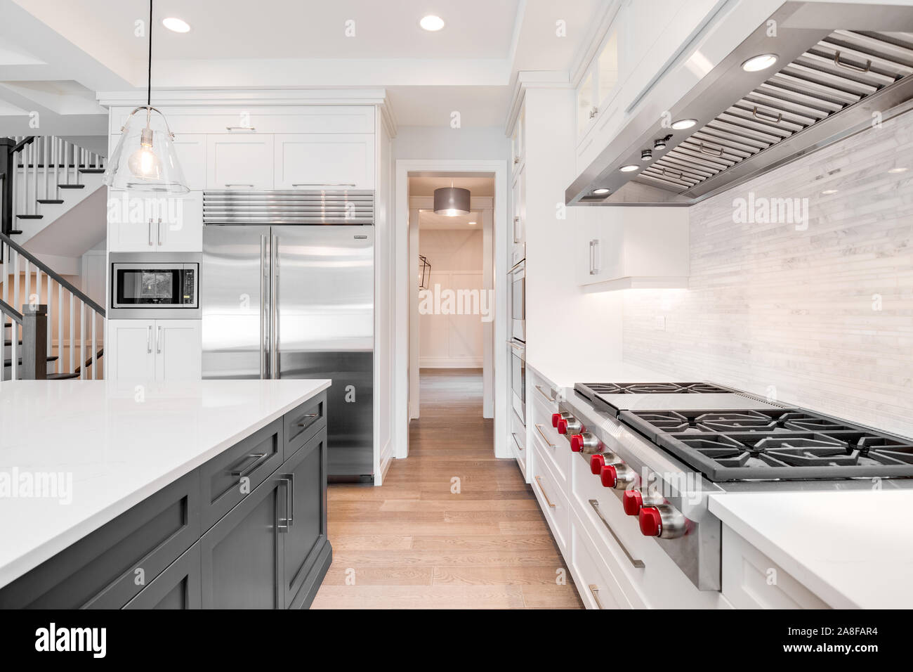 A luxurious modern kitchen with stainless steel Wolf appliances surrounded by white cabinets, beautiful granite, and hardwood floors. Stock Photo