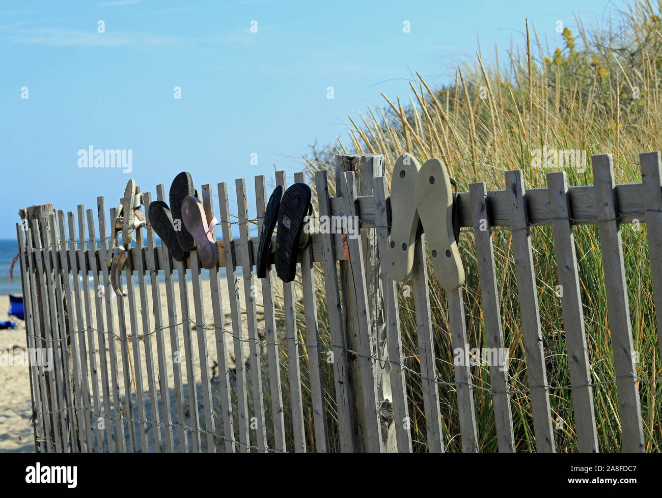 Flip-flops adorning a rickety wooden fence protecting dunes along the sandy path entrance to Nauset Light Beach on Cape Cod in Eastham, Massachusetts Stock Photo