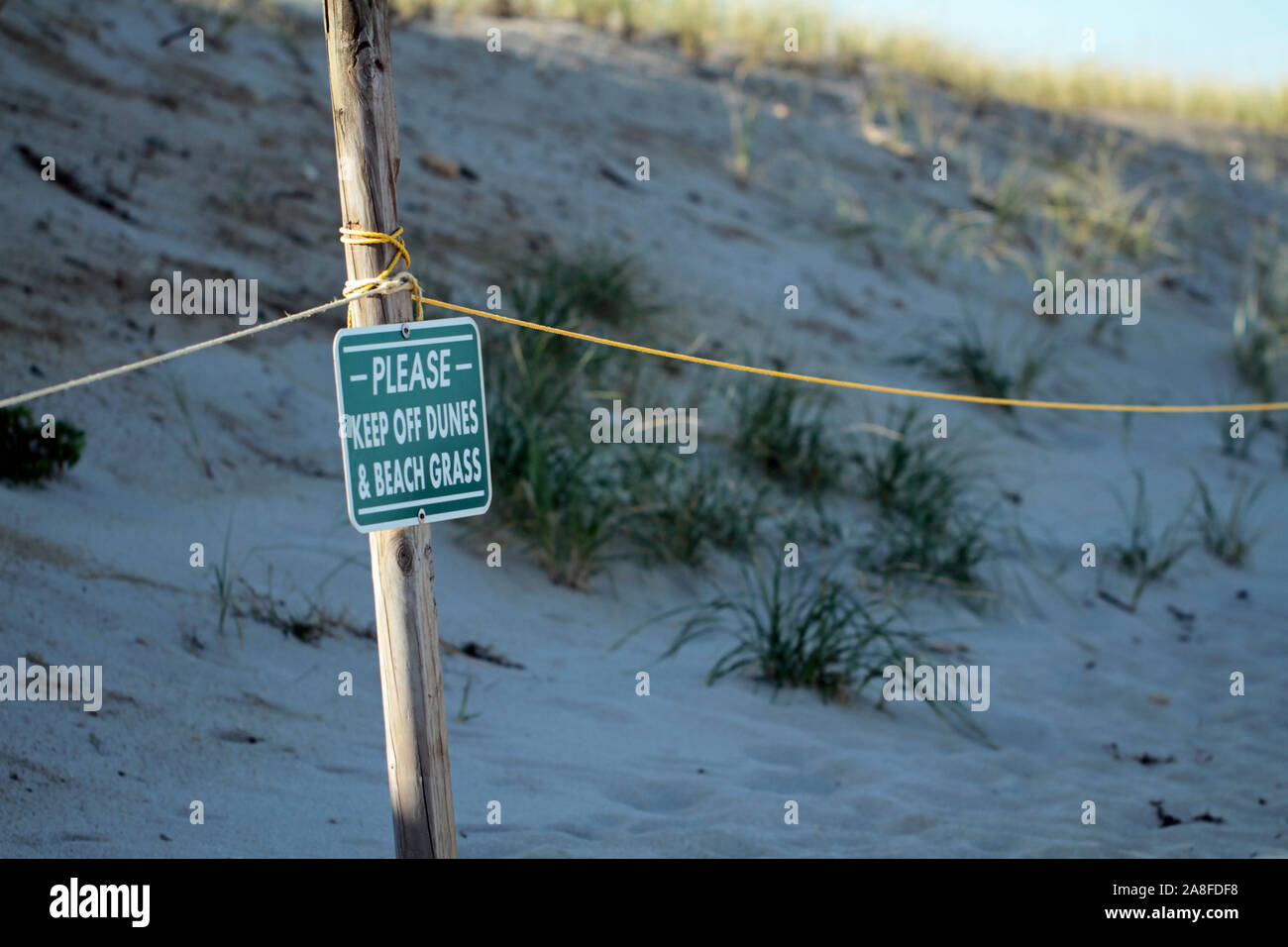 Roped off area with posted warning sign marking protected sand dunes and beach grass at Nauset Beach, Orleans, Massachusetts Stock Photo