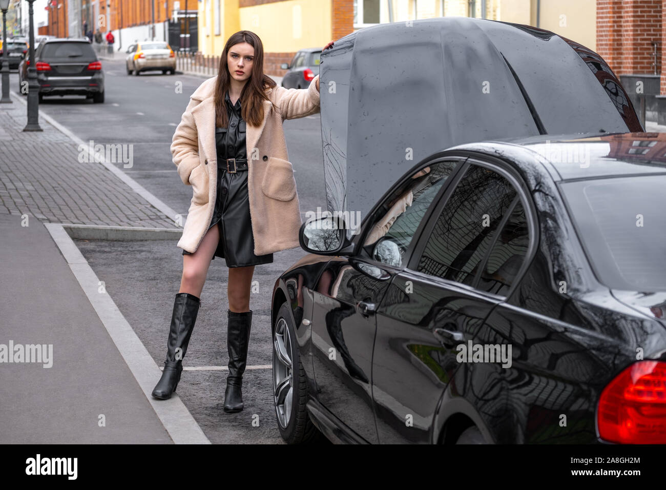 Woman waiting support near her broken car. a young woman stands near her broken car and does not know what to do with it.The car opened the hood. Stock Photo