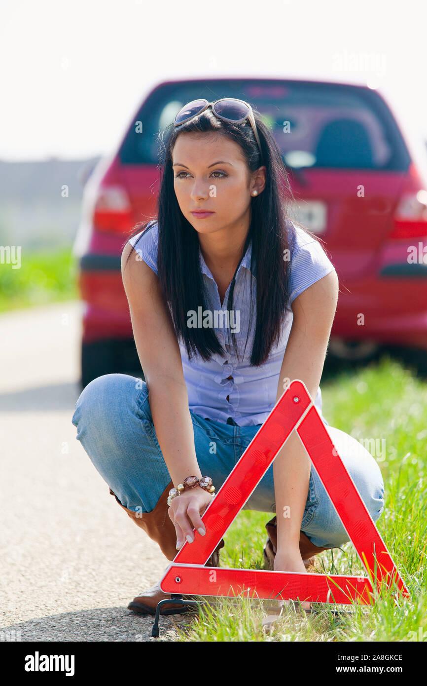 Junge Frau mit einem Warndreieck bei einer Autopanne, 25, 30, Jahre,  MR: Yes Stock Photo