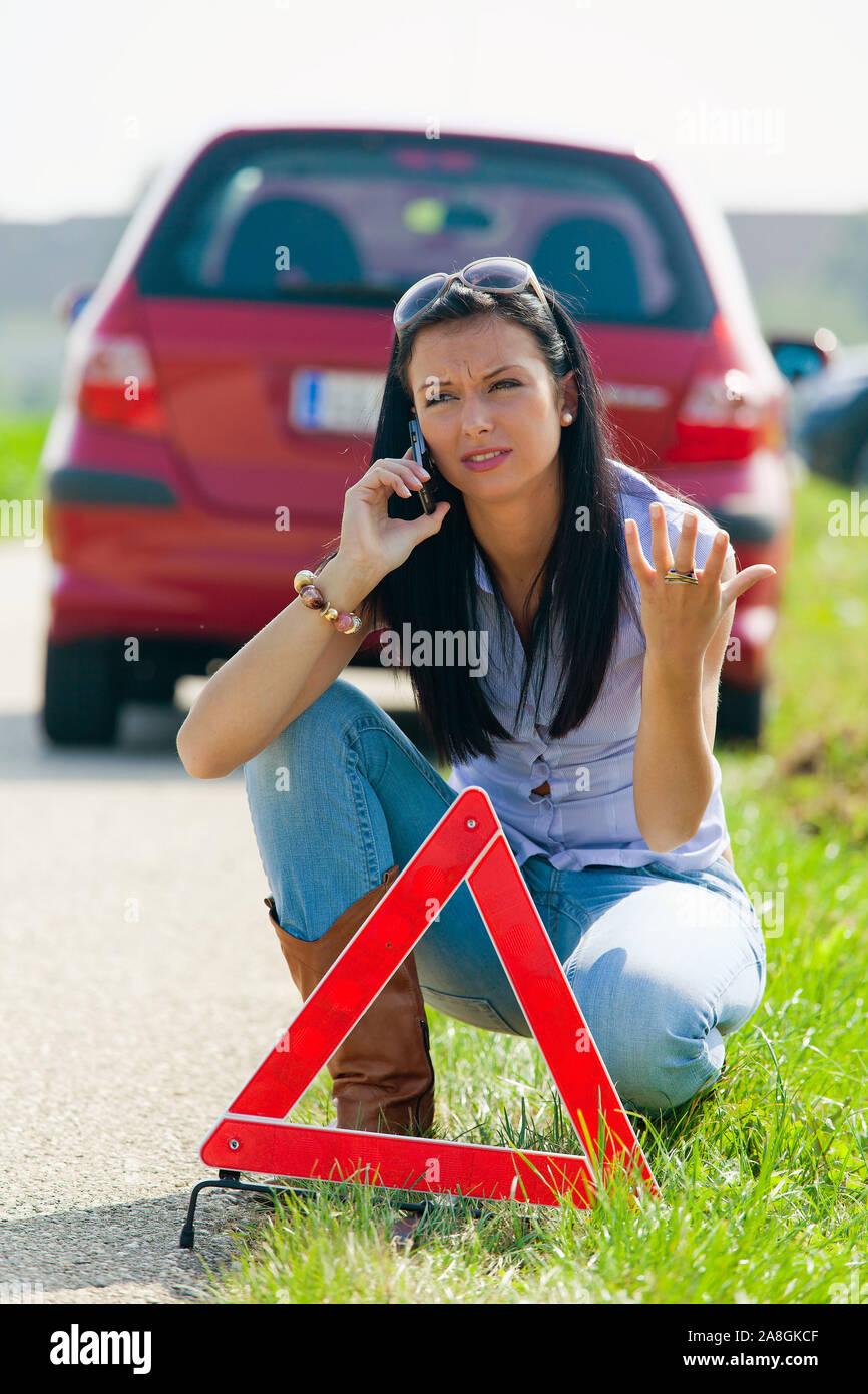 Junge Frau, 25, 30, Jahre,  mit einem Warndreieck bei einer Autopanne, MR: Yes Stock Photo