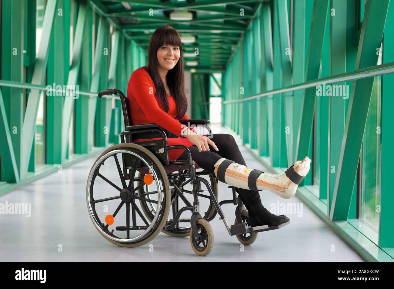 Junge Frau mit Gipsbein sitzt im Rollstuhl, 25, 30, Jahre, MR:Yes Stock Photo