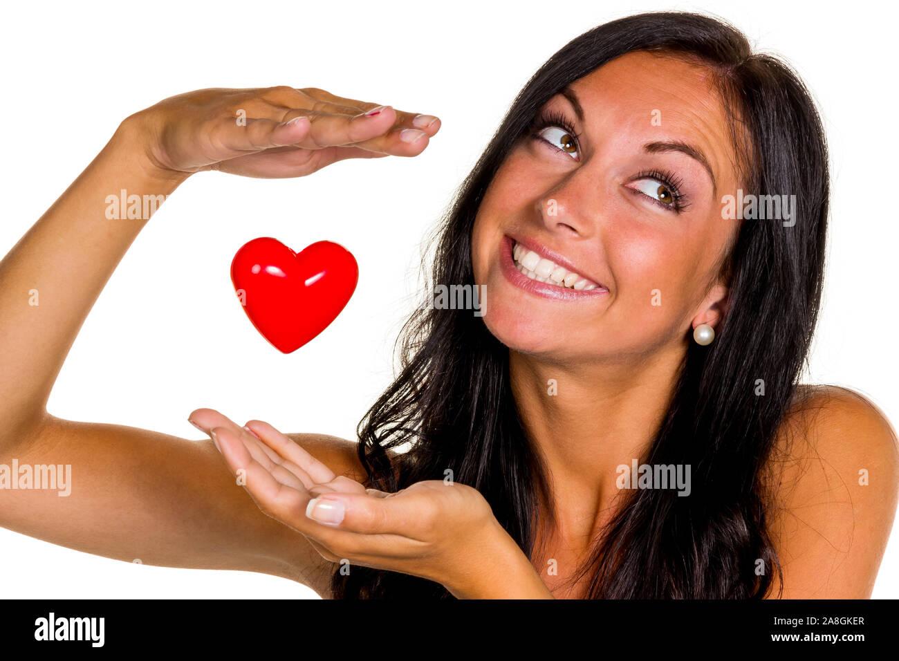 Eine verliebte junge Frau hält ein Herz in der Hand, 20, 25, Jahre, MR: Yes Stock Photo