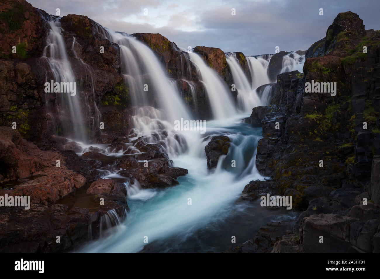 One of my favorite waterfalls in Iceland. Red rocks and blue water. Amazing contrasts... Stock Photo