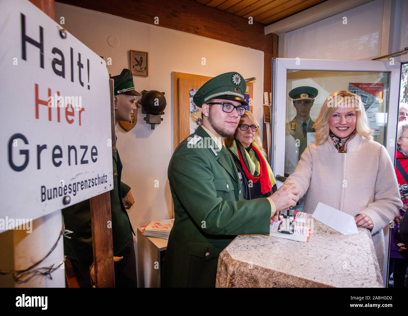09 November 2019, Schleswig-Holstein, Lübeck-Schlutup: Manuela Schwesig (SPD), the Prime Minister of Mecklenburg-Western Pomerania, receives an exit stamp from a Federal Border Guard to the GDR at the Border Museum near the former Schlutup border crossing during a celebration commemorating the fall of the Berlin Wall 30 years ago. Schlutup was at the time the northernmost border crossing via which GDR citizens flocked to the West after the surprising opening of the border. Photo: Jens Büttner/dpa-Zentralbild/dpa Stock Photo