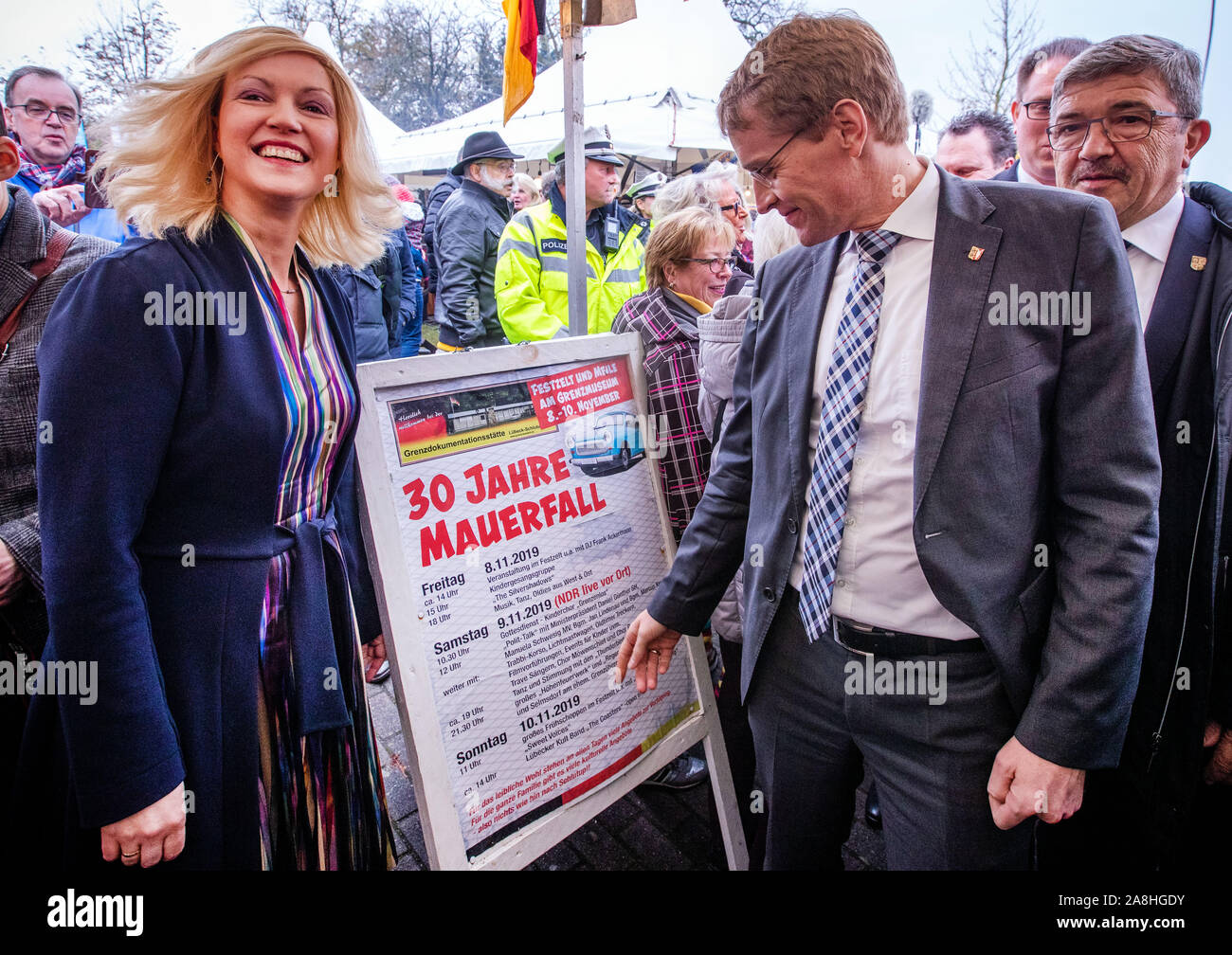 09 November 2019, Schleswig-Holstein, Lübeck-Schlutup: Manuela Schwesig (SPD), Prime Minister of Mecklenburg-Vorpommern, and Daniel Günther (CDU, r), Prime Minister of Schleswig-Holstein, are standing on the event poster at the border museum near the former Schlutup border crossing, celebrating the fall of the Berlin Wall 30 years ago. Schlutup was at the time the northernmost border crossing via which GDR citizens flocked to the West after the surprising opening of the border. Photo: Jens Büttner/dpa-Zentralbild/dpa Stock Photo