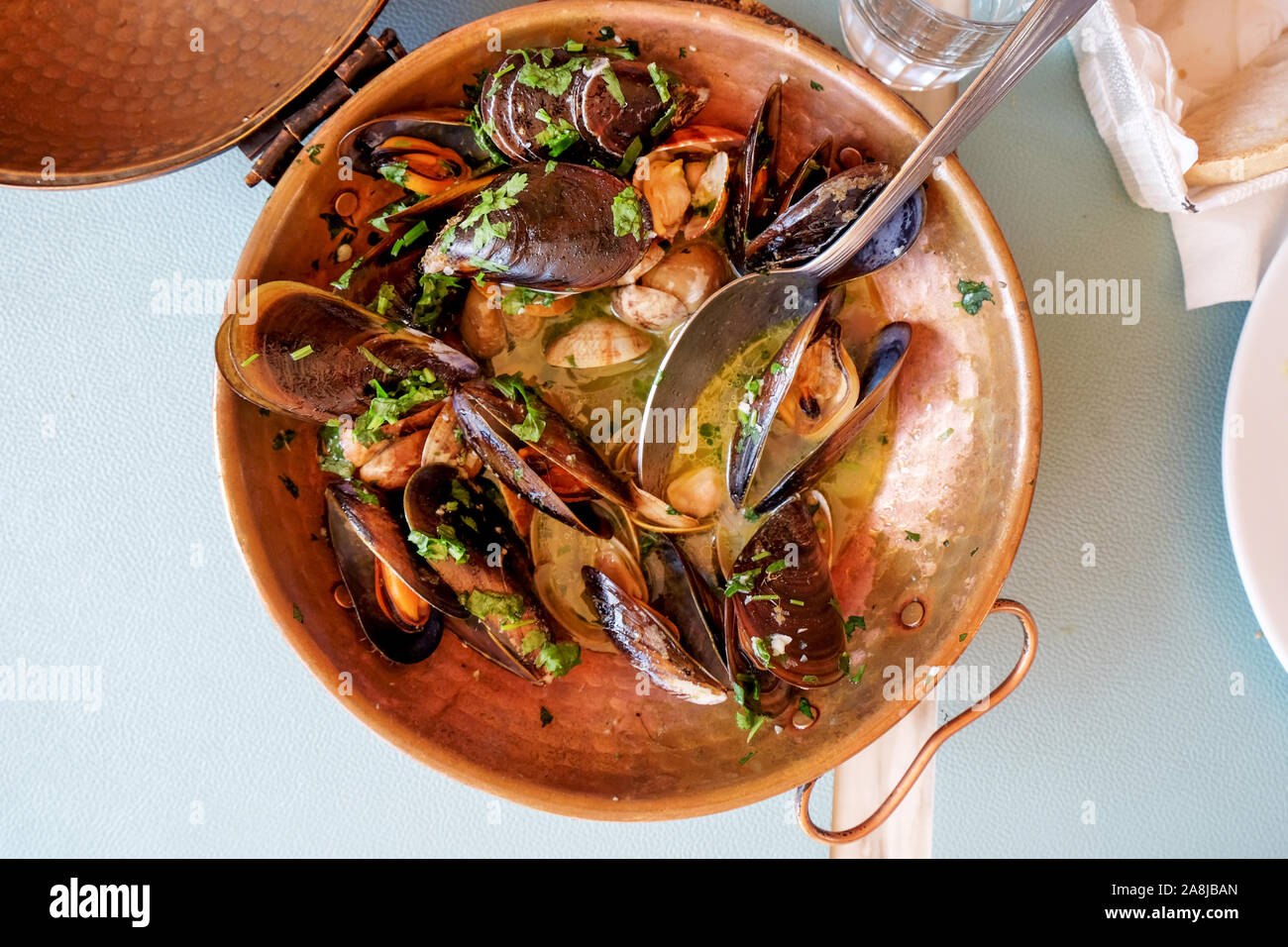 a restaurant copper serving bowl full of mussels and clams cooked in white wine sauce with garlic and parsley a traditional Portuguese dish called Ame Stock Photo
