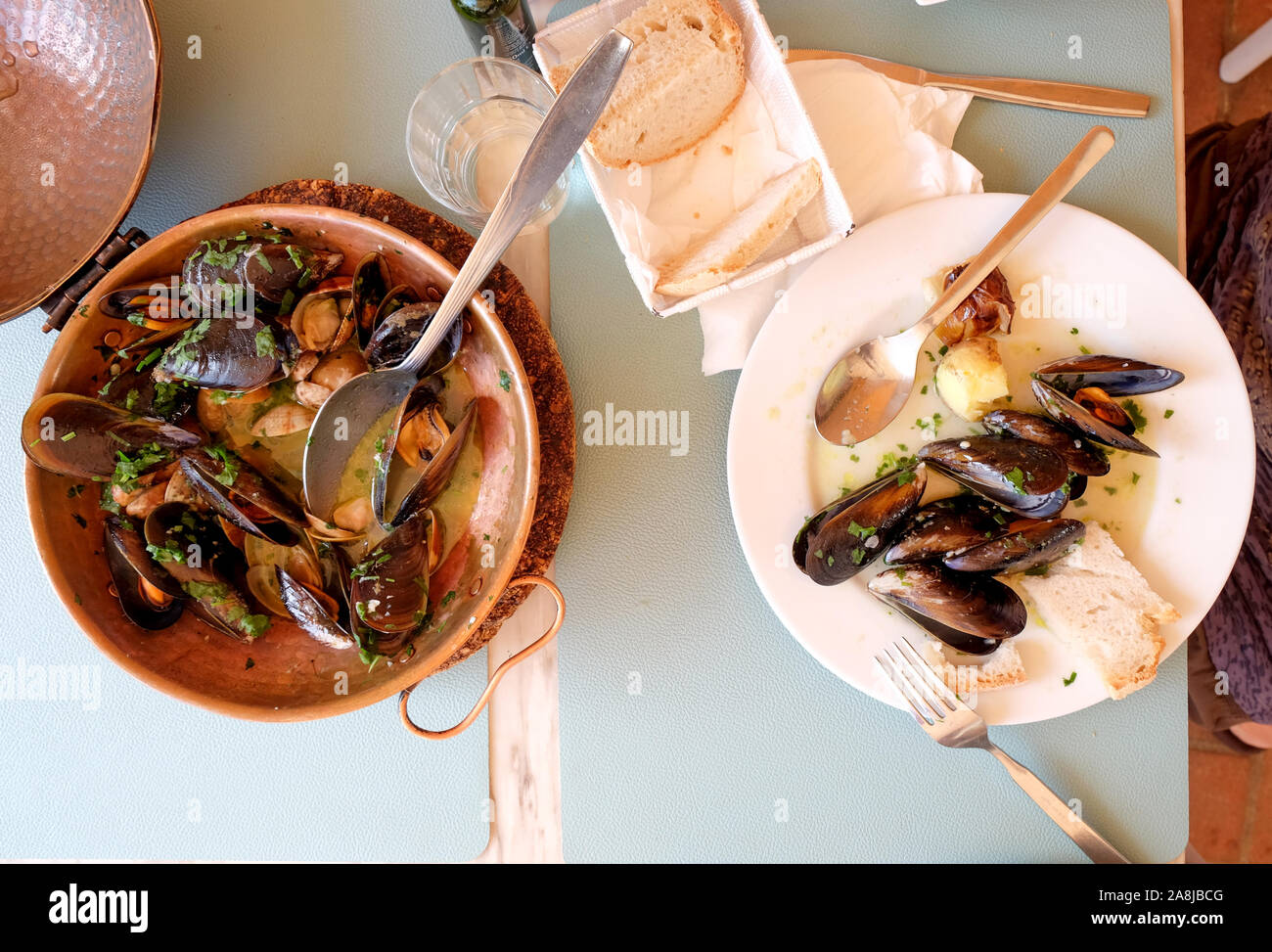 a restaurant table with a copper serving bowl and white plate full of mussels and clams, garlic and parsley a traditional Portuguese dish called Ameij Stock Photo