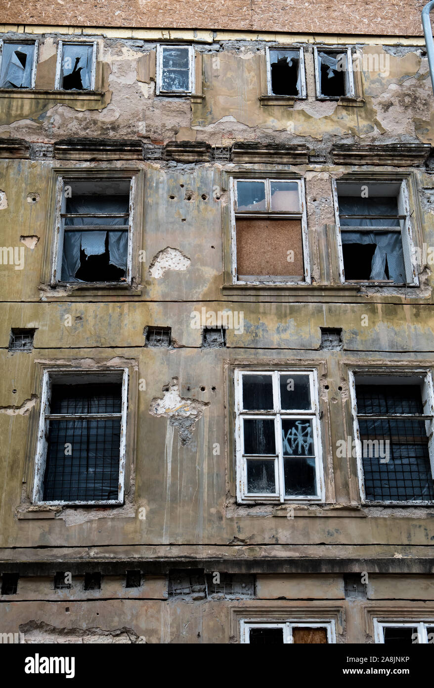 Old Desolate Apartment House With Damaged Facade And Bursted Windows Stock Photo