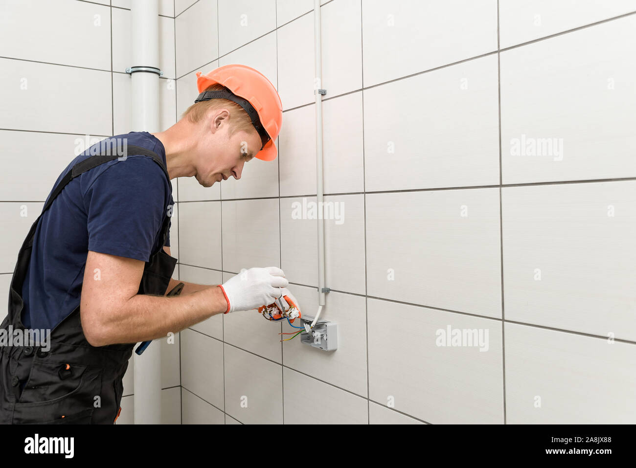 The electrician is installing an electrical outlet on the wall. Stock Photo