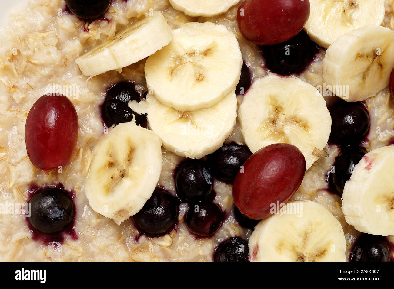 Oatmeal Breakfast With Bananas Blueberries And Red Grapes Isolated On White Background And Photographed From Directly Above Stock Photo Alamy