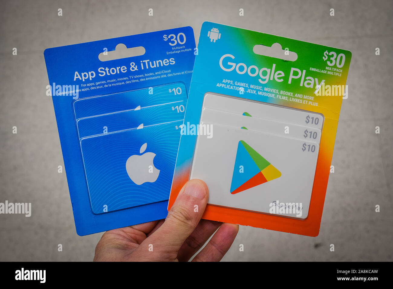a hand holding apple and google play store gift cards Stock