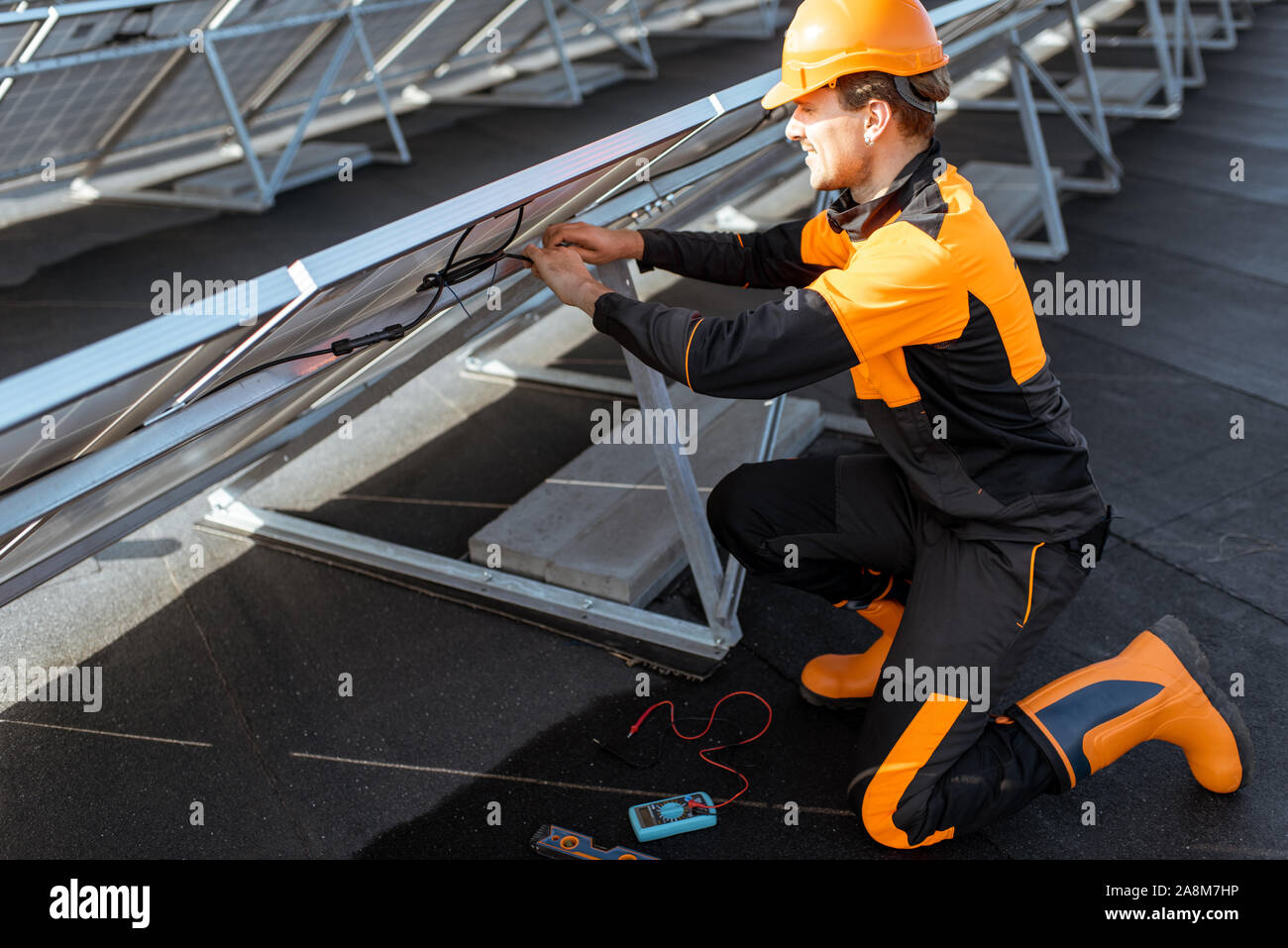 Well-equipped electrician connecting wires of solar panels on a rooftop photovoltaic power plant. Concept of installing solar stations Stock Photo