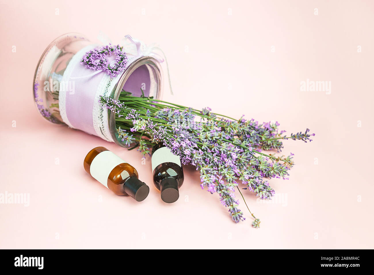 Natural cosmetics. Fresh lavender flowers and bottles essential oil or serum on pastel pink background. Alternative home medicine. Close-up, vintage style. Stock Photo