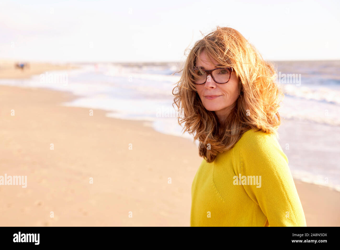 Close-up portrait of beautiful smiling mature woman with frizzy hair walking on the beach and enjoying sunrise. Stock Photo