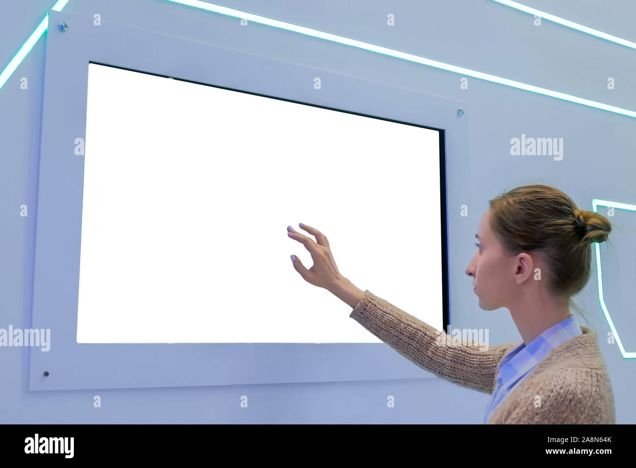 Woman touching blank white display wall at exhibition - white screen concept Stock Photo