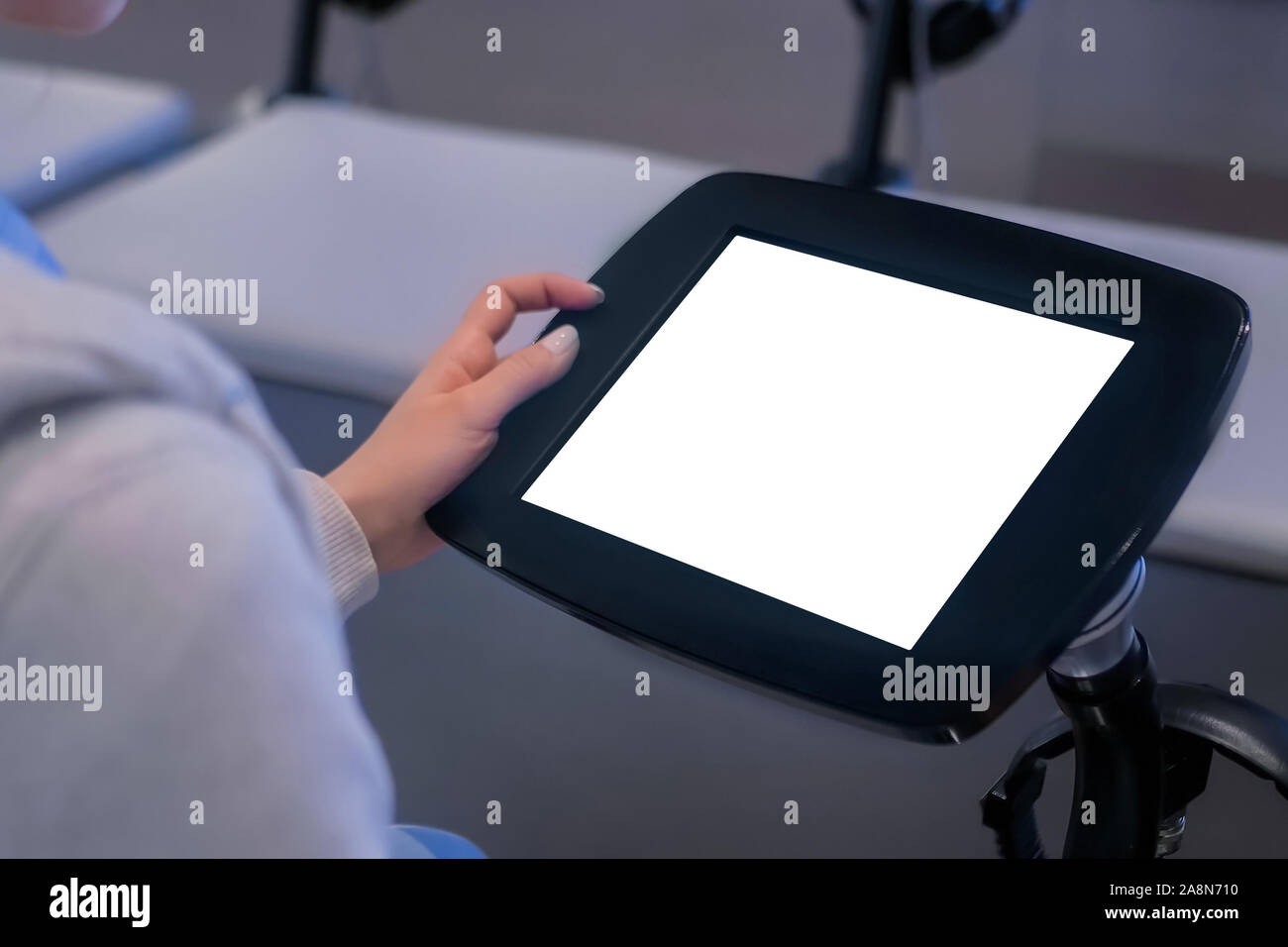 Woman looking at floor standing black tablet kiosk with blank white display Stock Photo