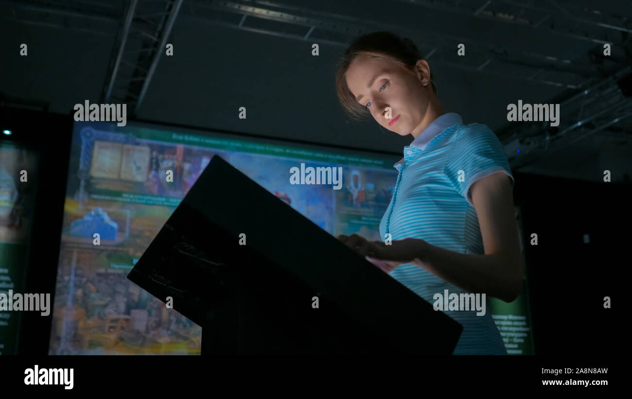 Woman using interactive touchscreen display at modern history museum Stock Photo
