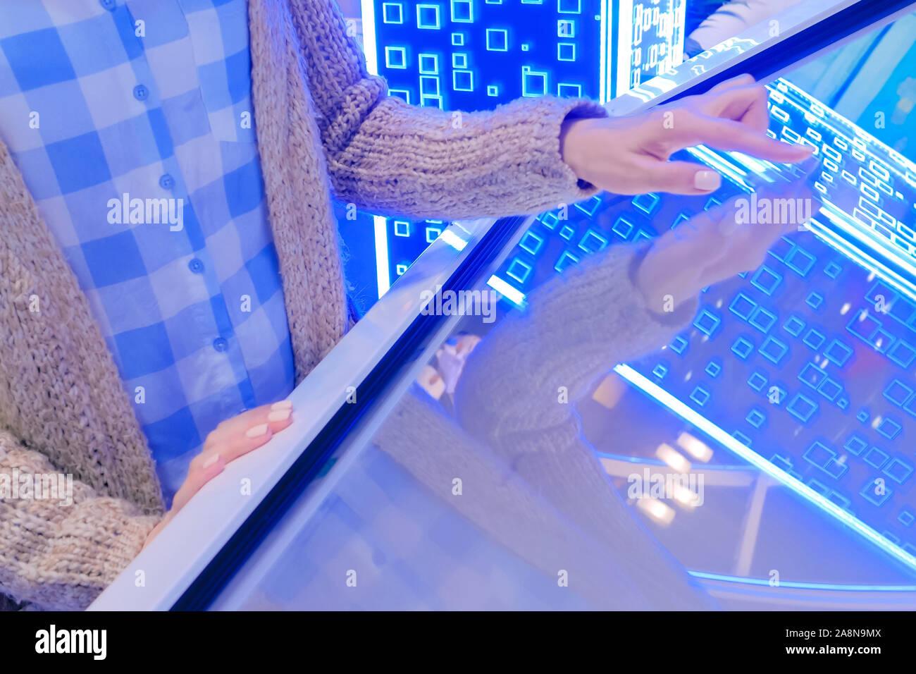 Woman using multimedia touchscreen display of interactive kiosk Stock Photo