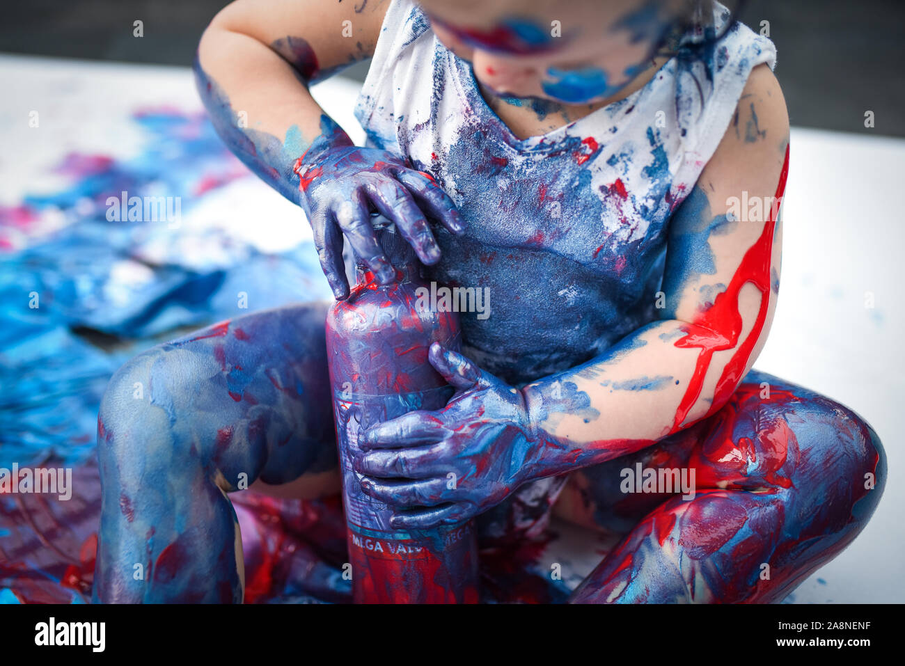 An adorable little toddler, girl has fun playing with colouring paints, getting messy and  having lots of fun, shot in a home environment Stock Photo