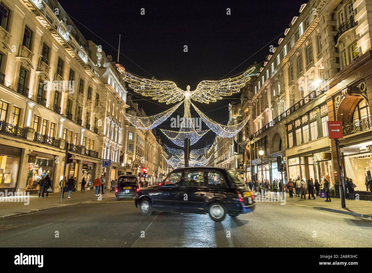 LONDON, UK - 17TH NOVEMBER 2018: Views along Regent Street at night showing Christmas decorations along the street. A typical London Black Cab can be Stock Photo