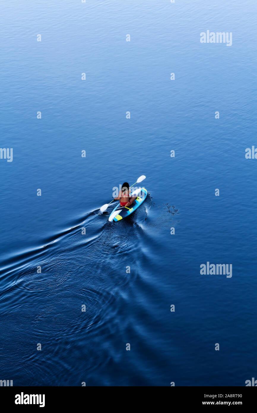 Woman In Red Bikini Sitting On Paddle Board With Kayak Oar Paddling On Blue Water With Wake Stock Photo