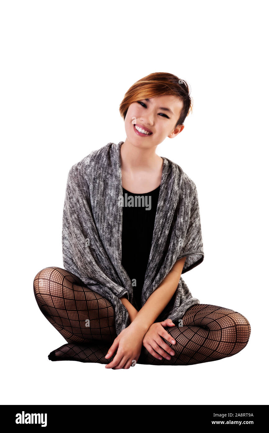 Smiling Slim Asian Woman Gray Sweater Sitting On White Background With Fishnet Stockings Stock Photo