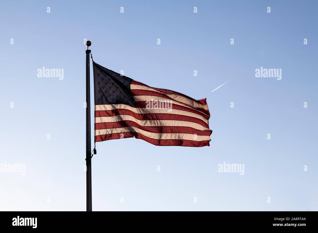 USA Flag Flying On Flagpole Backlit In Blue Sky With Jet Stream In Distance Stock Photo