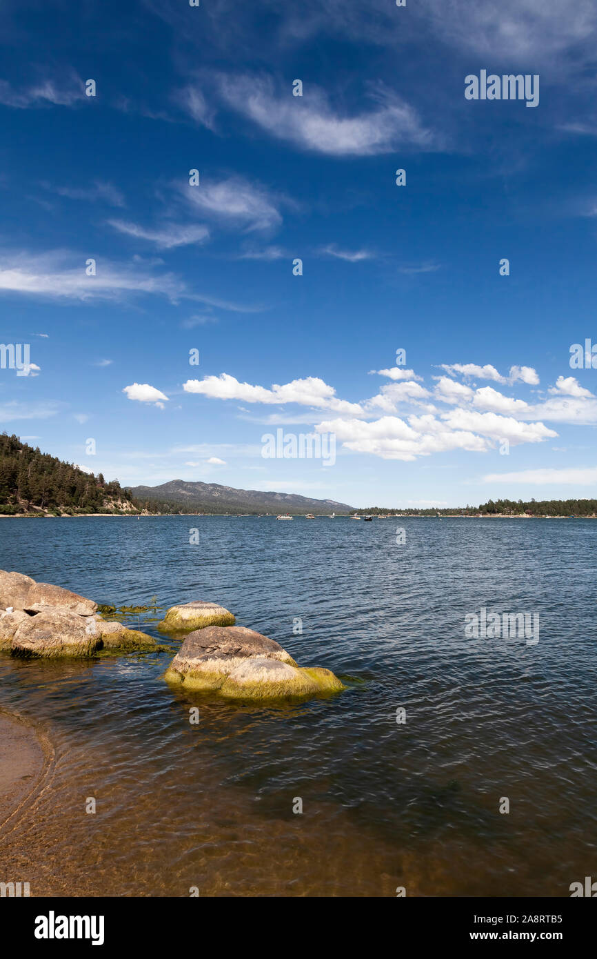 Vertical Landscape Big Bear Lake With Rocks Boats Blue Sky And White Clouds Stock Photo