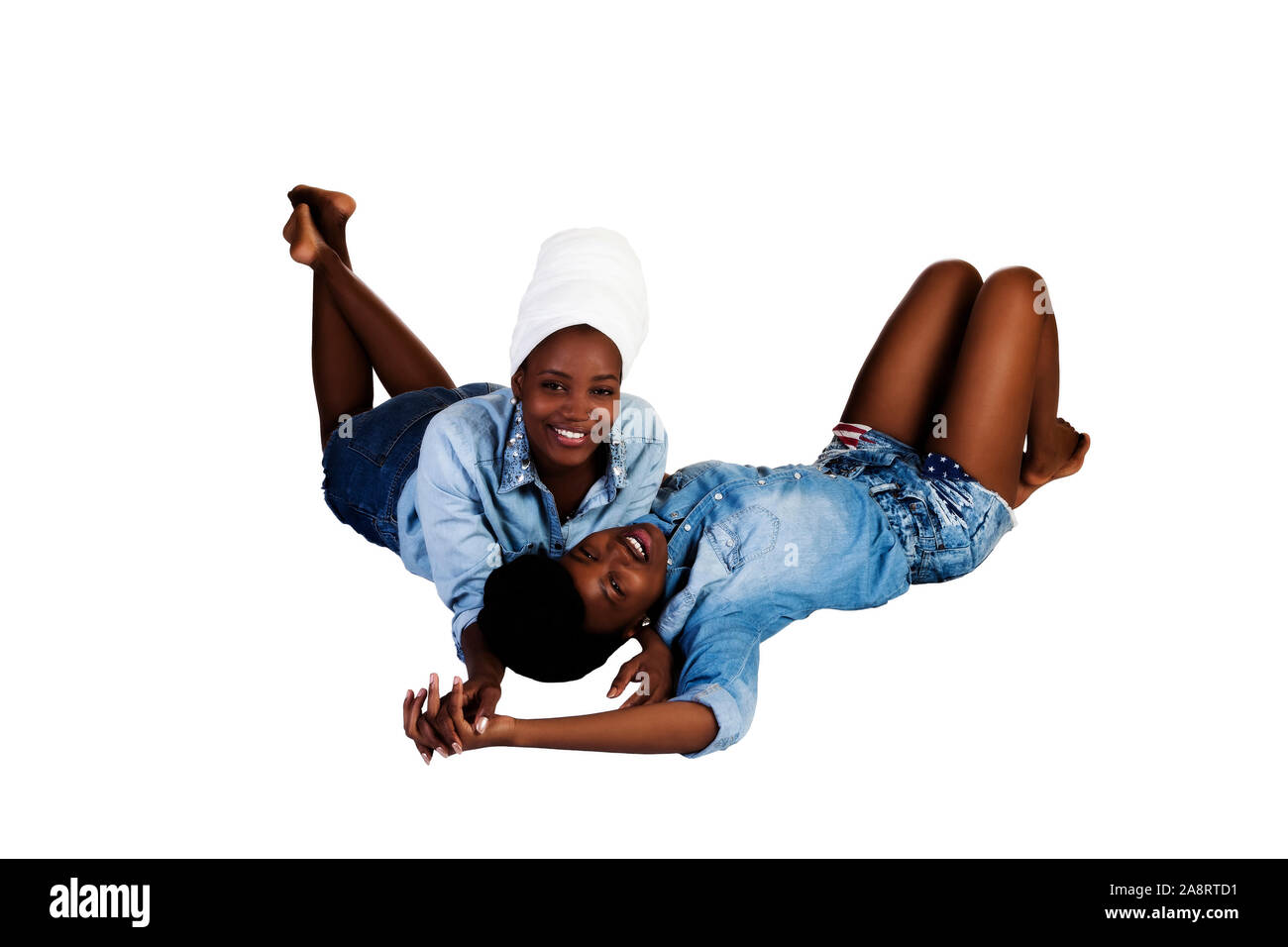 Two African American Sisters Reclining On A White Background In Head Scarfs Shorts And Blue Shirts Stock Photo