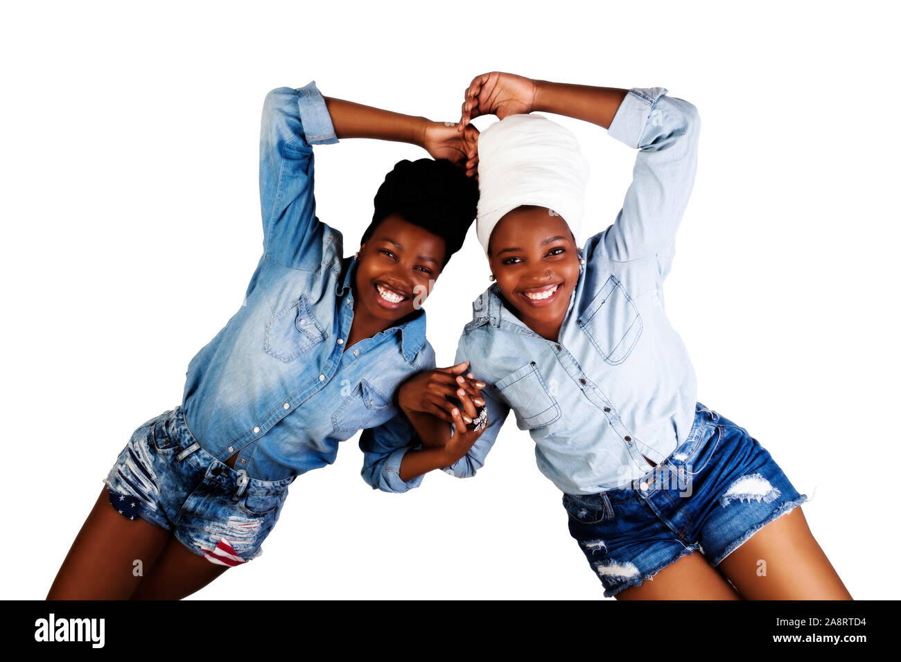 Two African American Sisters Reclining On A White Background In Head Scarfs Shorts And Blue Shirts Big Smiles Stock Photo