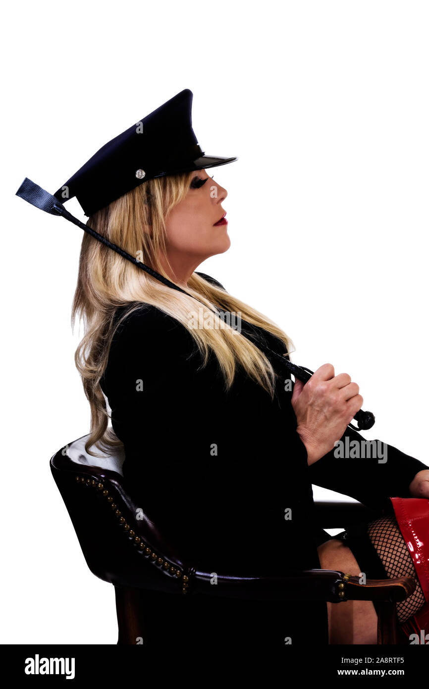 Middle Aged Caucasian Blond Woman Sitting In Chair Profile With Riding Crop Jacket And Fishnet Stockings Stock Photo