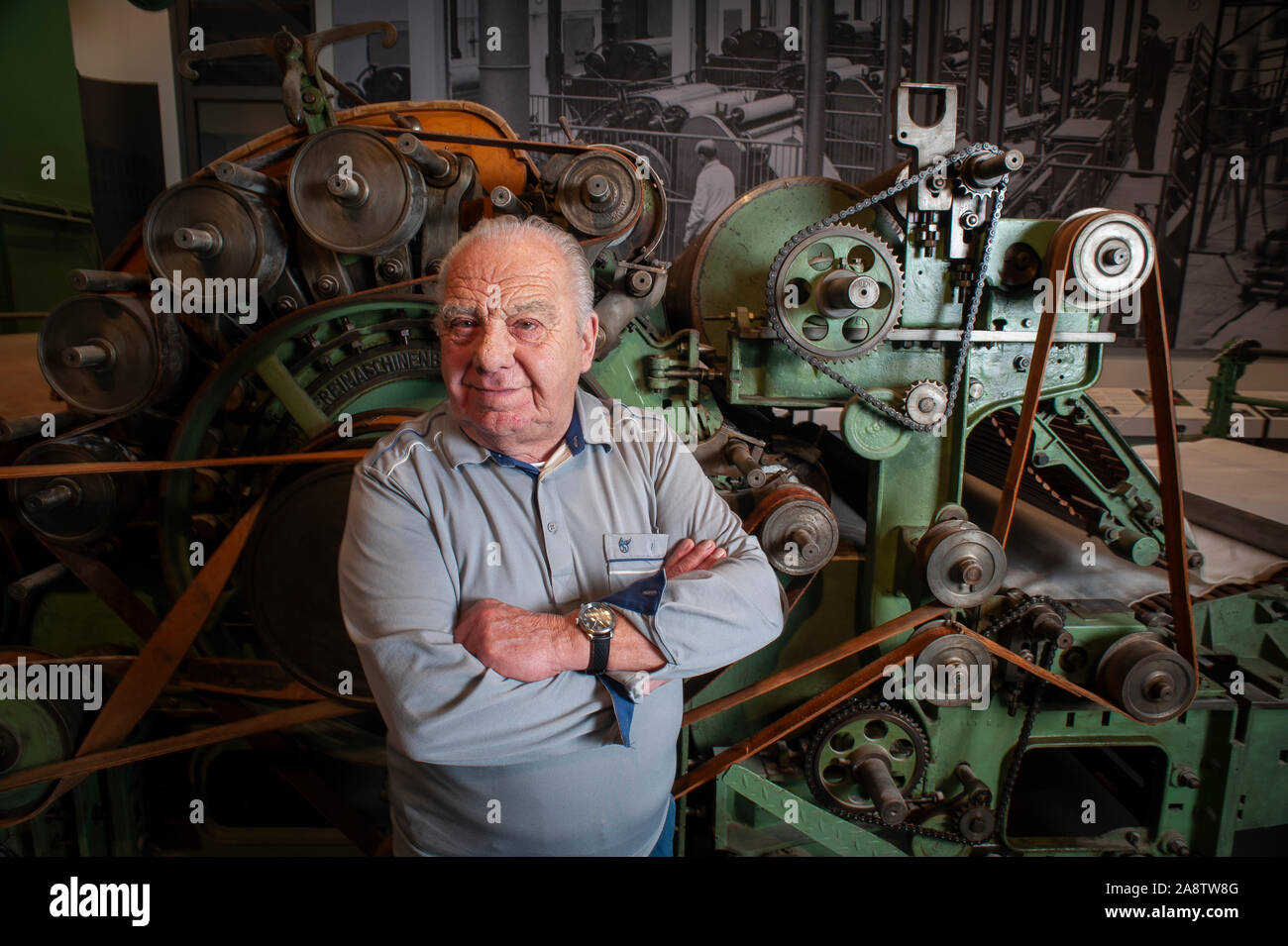83 year Roland Schulze who worked on the production of the East German Trabant in the time of the DDR stands beside some of the machinery used. Stock Photo