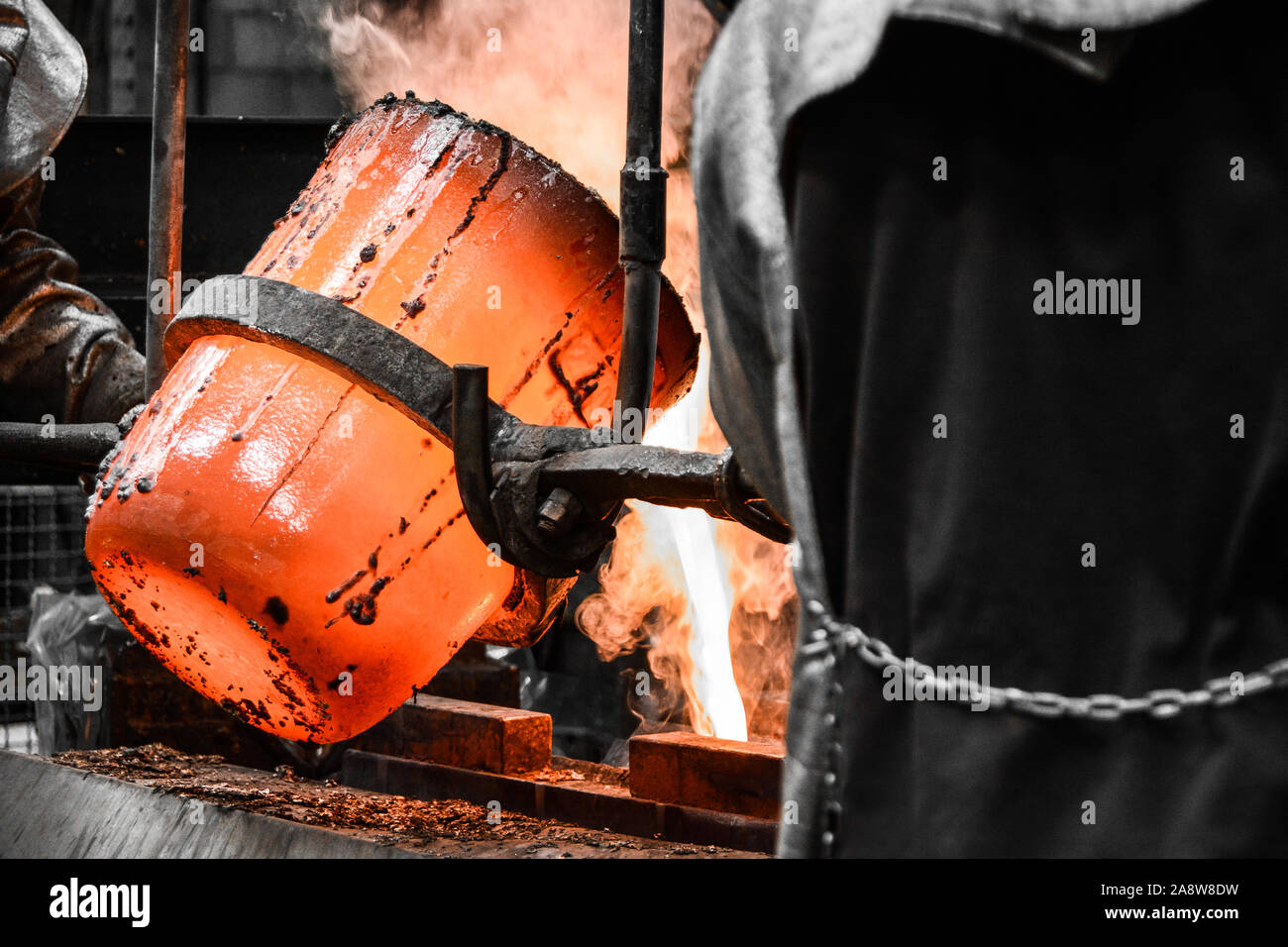 In a foundry workshop. The molten metal is poured into a mold from a crucible maneuvered by two workers Stock Photo